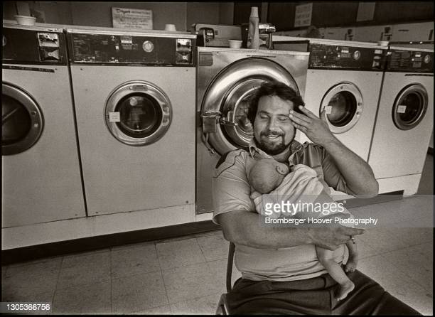 View of an unidentified man, his infant child in his arm, as she sits in a laundromat, Livermore, California, 1987.