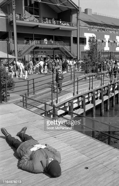 View of an unidentified man, his knit cap pulled down over his eyes, as he lies in a pedestrian walkway for a nap at Pier 17, South Street Seaport,...