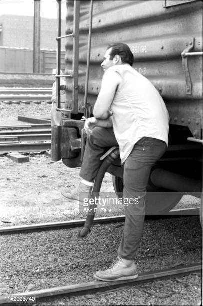View of an unidentified man, one leg on a boxcar, as he stands on train tracks to wait for Robert F Kennedy's funeral train, Elizabeth, New Jersey,...