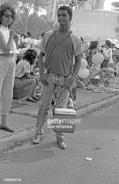 View of an unidentified man, with a small cooler in his hand, as he stands on a foot path in Flushing Meadows Park, in the Corona neighborhood of...