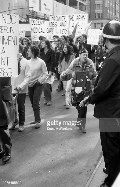View of an unidentified police officer from the New York City Police Department standing guard with nightstick in hand as anti-war demonstrators...
