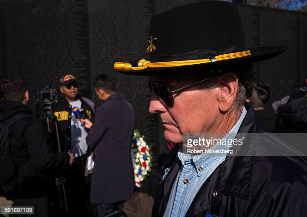 View of an unidentified visitor in sunglasses and a US Army Cavalry hat at the Vietnam Veterans Memorial Wall during the Veterans Day observance...