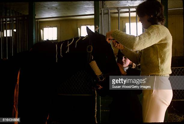 View of an unidentified woman and girl both in equestrian clothing as they groom a horse in a stable on Harry de Leyer's Long Island farm Smithtown...