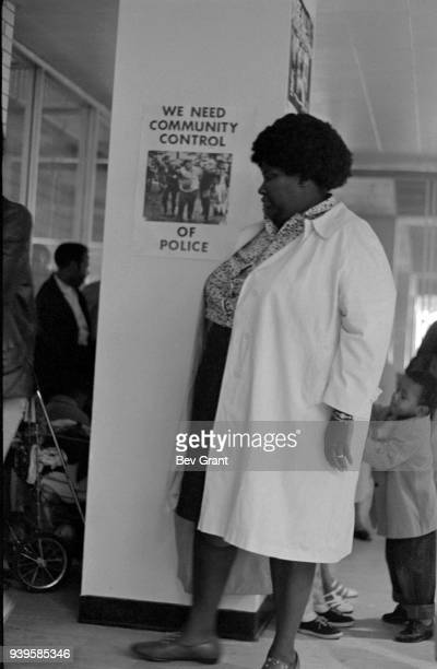 View of an unidentified woman as she attends a clothing drive sponsored by the Black Panther Party New York New York July 28 1969 A poster on the...