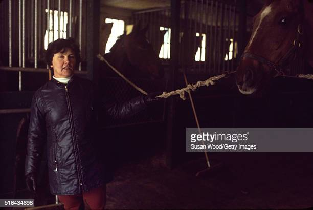 View of an unidentified woman as she stands in a stable on the grounds of Harry de Leyer's Long Island farm Smithtown New York 1976 De Leyer famously...