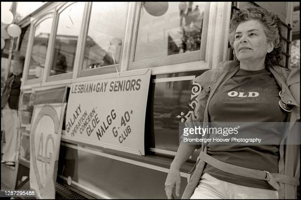 View of an unidentified woman, in a t-shirt that reads 'Old,' as she steps off a streetcar with a sign that reads, in part, 'Lesbian and Gay Seniors'...