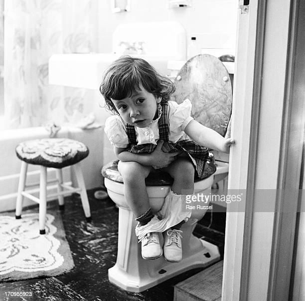 View of an unidentified young girl seated on a toilet and peeking out a bathroom door New York 1948