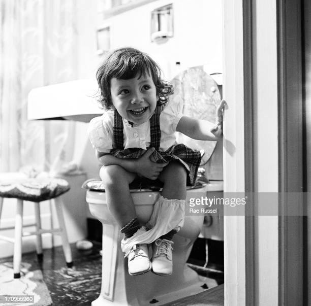 View of an unidentified young girl smiling as she looks out a bathroom door while seated on a toilet New York 1948