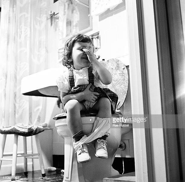 View of an unidentified young girl with her left hand obscuring her face while seated on a bathroom toilet New York 1948