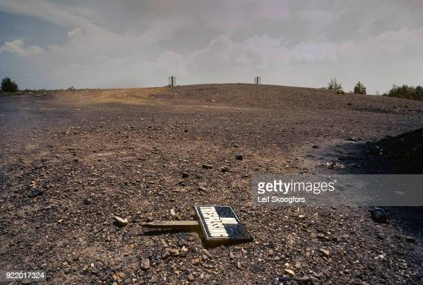 View of an uprooted 'No Trespassing' sign on the ground in Centralia Pennsylvania 1983 The town was largely abandoned due to an underground coal seam...