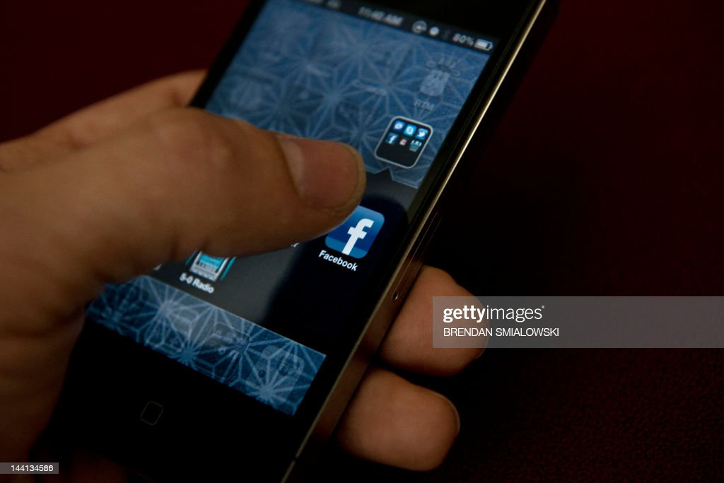 A view of and Apple iPhone displaying the Facebook app's splash screen May 10, 2012 in Washington, DC. Social-networking giant Facebook will go public on the NASDAQ May 18 with its initial public offering, trading under the symbol FB, in an effort to raise $10.6 billion.