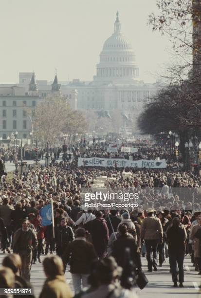 View of anti Vietnam War demonstrators pictured taking part in a march on a street in front of the United States Capitol building to protest against...