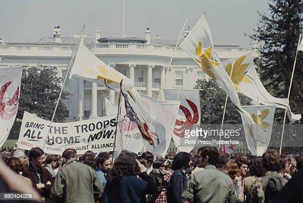 View of anti Vietnam war demonstrators standing and protesting outside the White House during a march to the Pentagon in Washington DC to plead for...