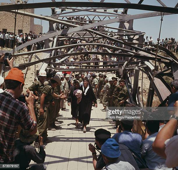 View of Arab and Jordanian refugees crossing the river Jordan via the wrecked Allenby or King Hussein bridge in August 1967 following the end of...