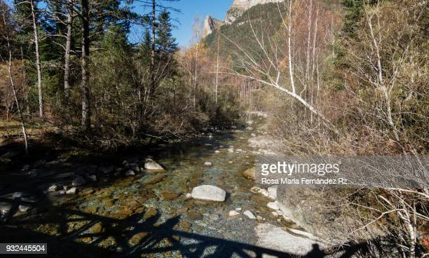 View of Aranzas river in Ordesa & Monte Perdido National Park and people silhouettes on bridge over it, Huesca, Pais Vasco, Northern of Spain, Europe