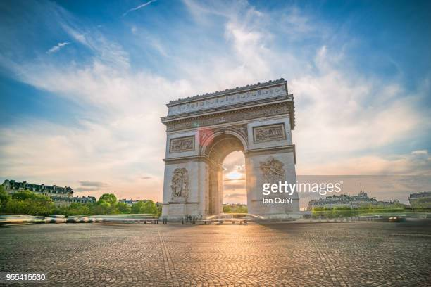 view of arc de triomphe in paris at sunset. - france stock-fotos und bilder