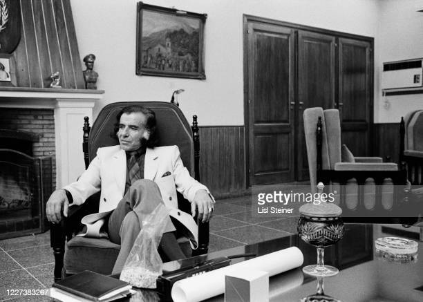 View of Argentinean politician Governor of La Rioja Carlos Menem as he sits in an armchair behind his desk Argentina 1988