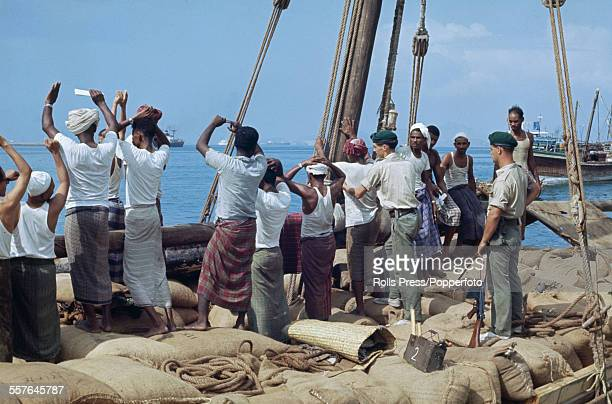 View of armed British troops and Marines searching the crew of a dhow for terrorist weapons off the coast of Aden town following a period of unrest...