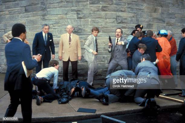 View of armed Secret Service agents around the bodies of policeman Thomas K Delahanty and White House Press Secretary James Brady outside the...