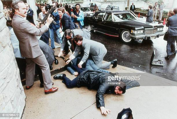 Secret Service agents and bystanders attend to those injured in the assassination attempt on Ronald Reagan by John Hinckley Jr Press Secretary James...