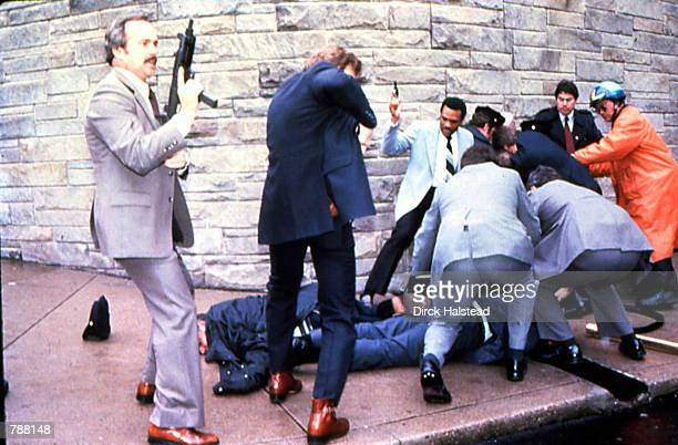 James Brady and a police officer are seen lying on the ground after being shot while the suspect John Hinckley Jr is apprehendedat right moments...