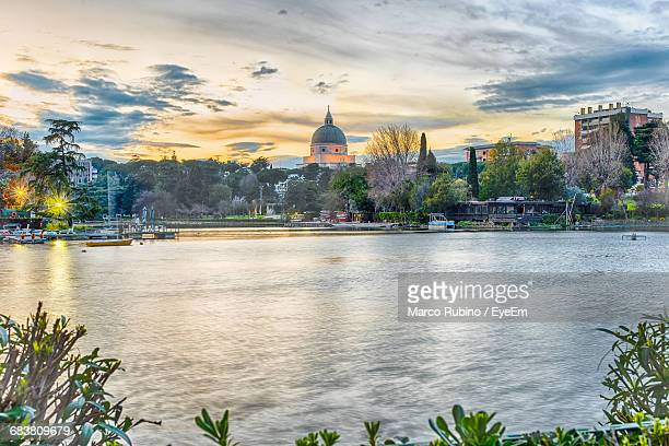 view of artificial lake and buildings in eur district against cloudy sky - eur rome stock pictures, royalty-free photos & images