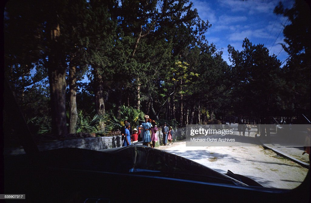A view of as women and children walk down the street, taken from a car in Bermuda.