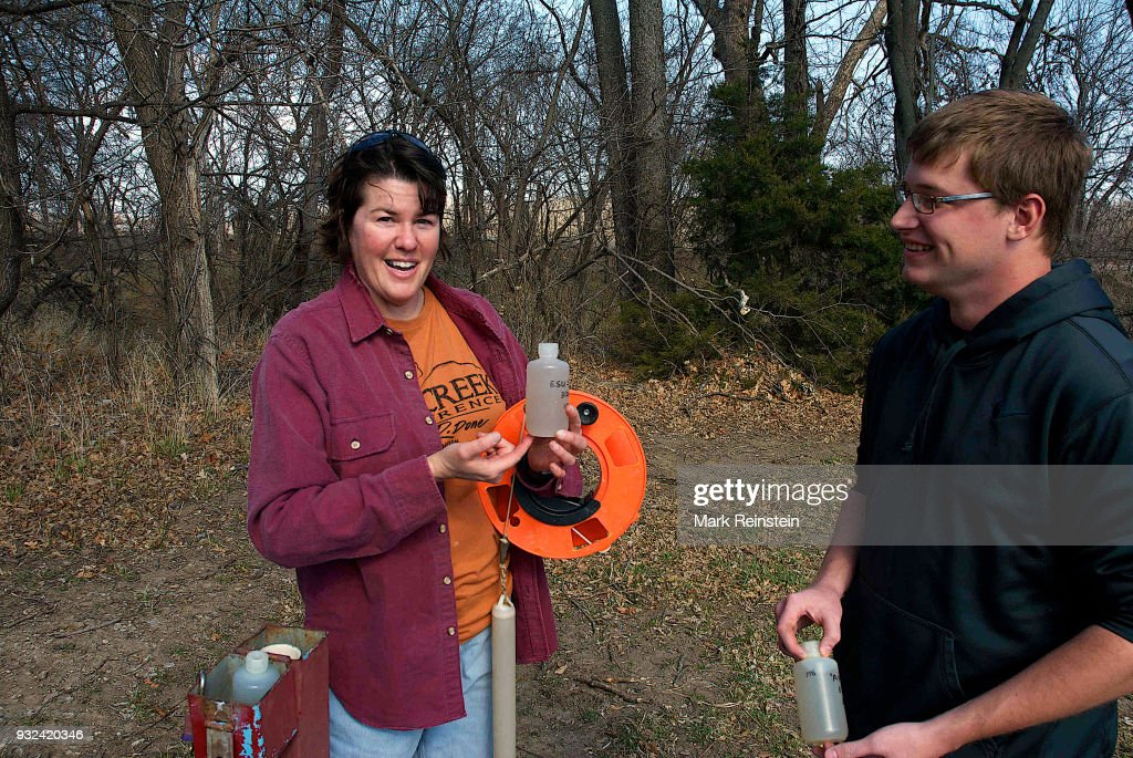 View of Associate Professor of Physical Science Dr Marcia Schlumeister (left) and her student Bryce Waggoner as they both hold sample containers at a test well on the grounds of Emporia State University, Emporia, Kansas, March 27, 2014. They had taken the samples to test the concentration levels of nitrogen and potassium in ground water.