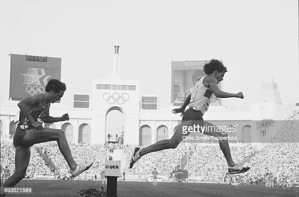View of athletes clearing the water jump hurdle hazard during competition in heat 1 of the Men's 3000 metres steeplechase event at the 1984 Summer...