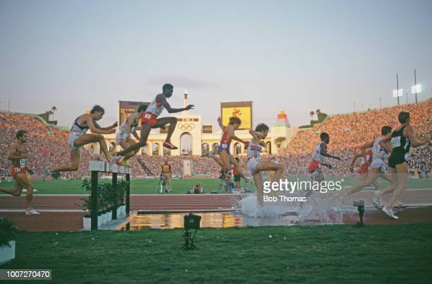 View of athletes clearing the water jump hurdle hazard during competition in the final of the Men's 3000 metres steeplechase event at the 1984 Summer...
