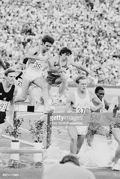 View of athletes competing in the final of the Men's 3000 metres steeplechase event with from left Peter Renner of New Zealand Colin Reitz of Great...