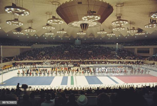 View of athletes from competing countries standing together and participating in the closing ceremony of the 1972 Winter Olympics inside the...