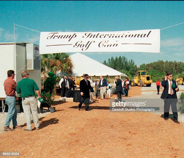 View of attendees under a banner and near the event tent at the site of the Trump International Golf Club groundbreaking ceremony Palm Beach Florida...