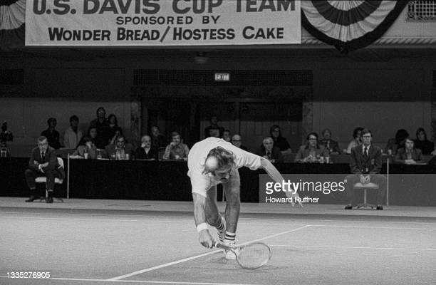 View of Australian tennis player John Newcombe as he reaches forward for a ball during a match on the first day of the 62nd Davis Cup final,...