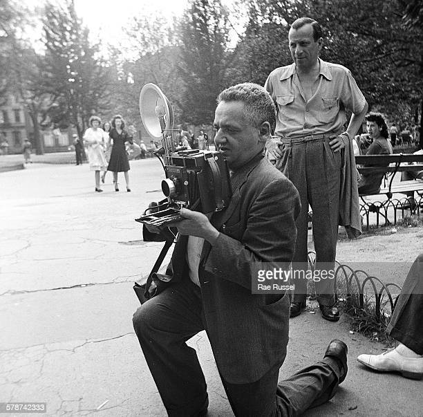 View of AustroHungarian born American photographer Weegee as he kneels down to line up a photograph in Washington Square Park New York New York 1945