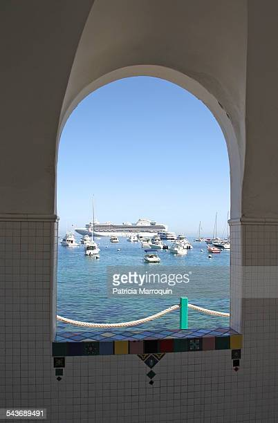 A view of Avalon Harbor boats yachts and a cruise ship through a tiled arched window on Catalina Island California