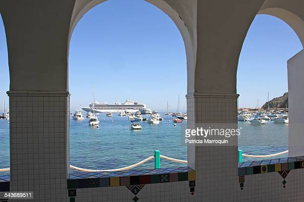A view of Avalon Harbor boats yachts and a cruise ship through tiled arched windows on Catalina Island California
