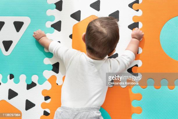 view of baby hand, arms and torso with cute clothing on a foam puzzle play mat during tummy time. - foam finger fotografías e imágenes de stock