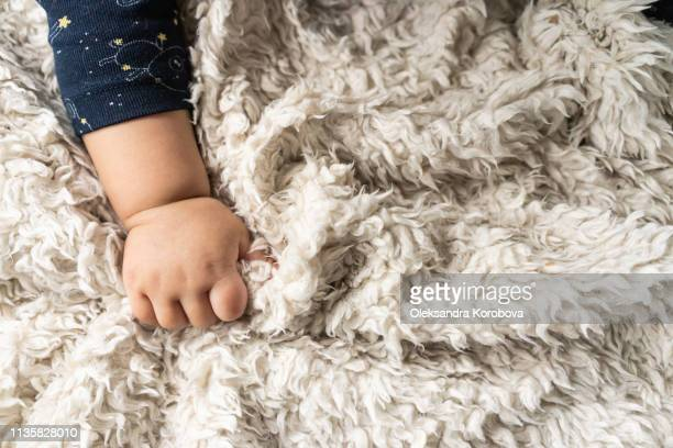 view of baby hand with cute clothing on a fur blanket during tummy time. - fragilidad fotografías e imágenes de stock