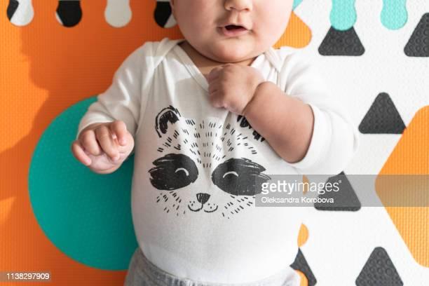 view of baby's torso, hands on a foam puzzle play mat. wearing a cute raccoon onesie and neutral pants. - foam finger fotografías e imágenes de stock