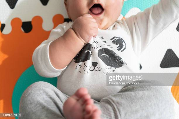 view of baby's torso, hands on a foam puzzle play mat. wearing a cute raccoon onesie and neutral pants. - hands in her pants stock pictures, royalty-free photos & images