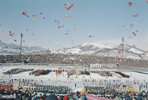 View of balloons being released in to the air as participating teams line up behind during the opening ceremony of the 1972 Winter Olympics in the...
