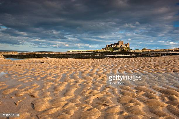 view of bamburgh castle from a sandy beach - northumberland stock pictures, royalty-free photos & images