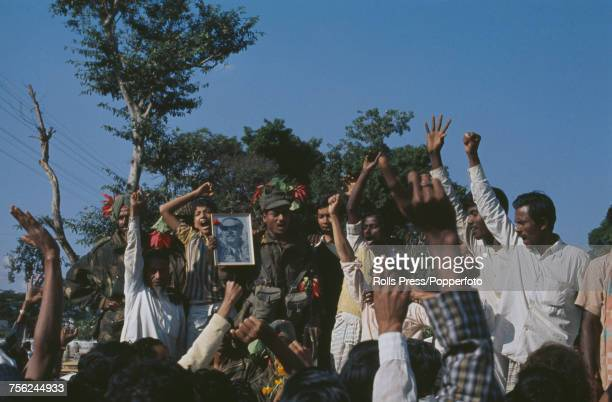 View of Bangladeshi guerillas and Indian Army troops gleefully cheering with a portrait of Sheikh Mujibur Rahman in Dacca in December 1971 The...
