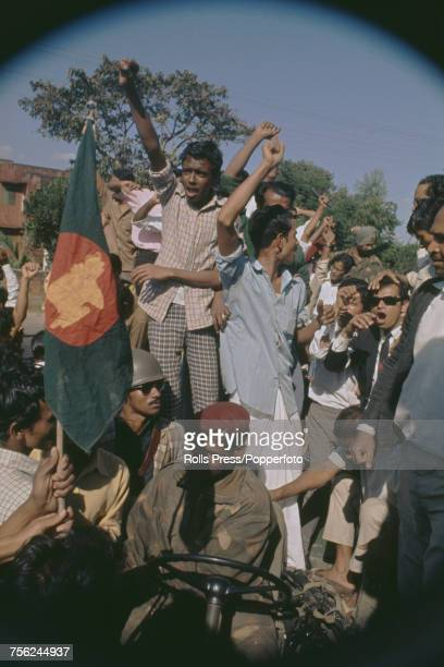 View of Bangladeshi guerillas gleefully waving the Bangladesh flag as they crowd on and around an Indian Army jeep in Dacca in December 1971 The...