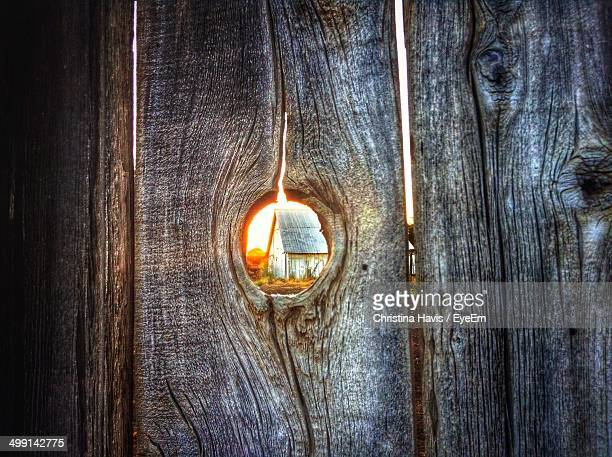 View of barn through hole in wooden fence