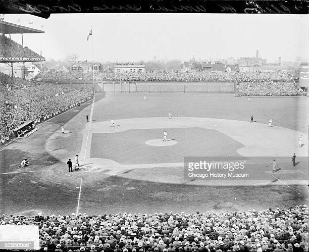 View of baseball players standing in position on the field during a 1929 World Series game between the National League's Chicago Cubs and the...
