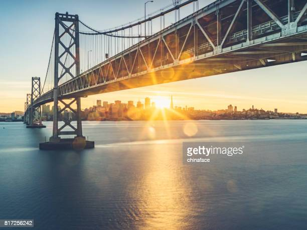 view of bay bridge and san francsico city skyline from yerba buena island - suspension bridge stock photos and pictures