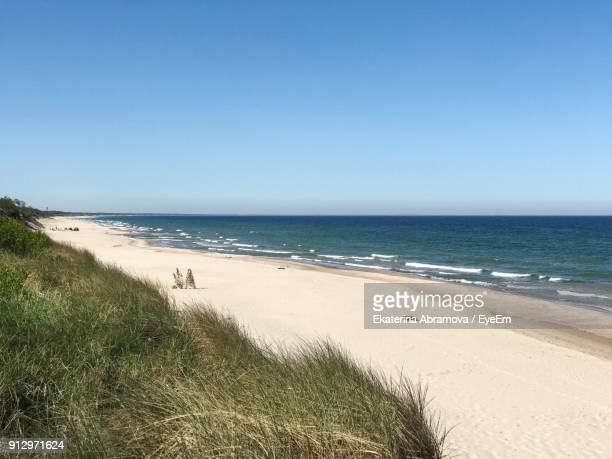 view of beach against clear blue sky - kaliningrad stock pictures, royalty-free photos & images