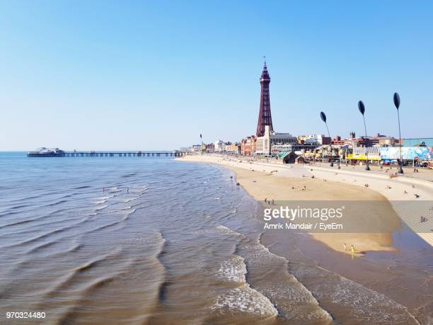 view of beach against clear blue sky - blackpool stock photos and pictures